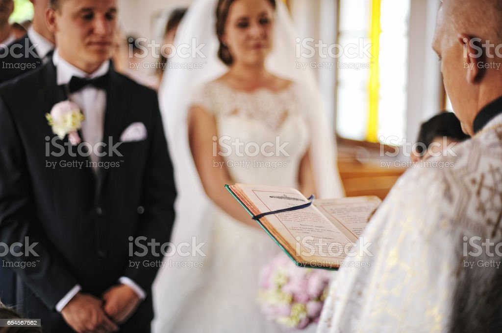 Priest read a holy bible book background newlyweds stock photo