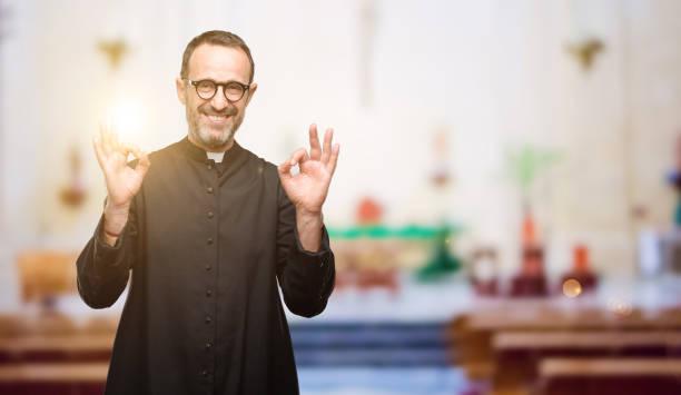 homem de religião sacerdote fazendo sinal okey gesto com ambas as mãos expressando a meditação e relaxamento - padre - fotografias e filmes do acervo