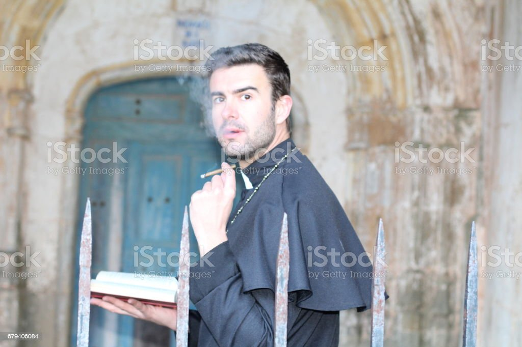 Priest smoking while taking a break stock photo