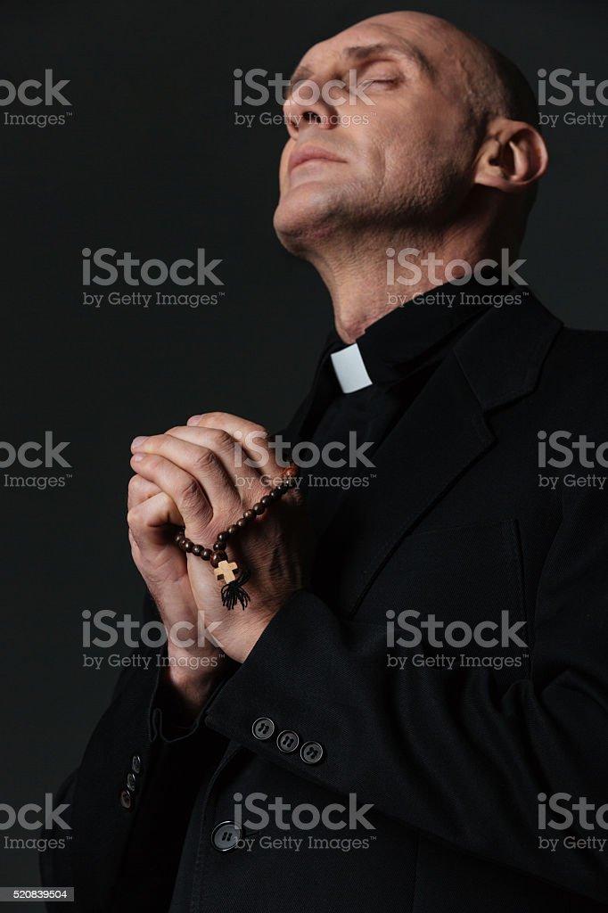 Padre em pé com olhos fechados e orar - foto de acervo