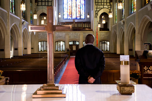 Priest waiting for a sign in church Priest waiting for a sign in church clergy stock pictures, royalty-free photos & images