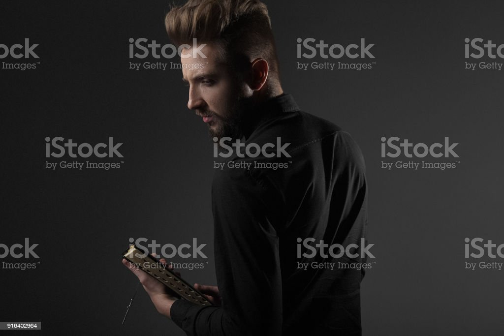 A priest with a bible in his hands looks away on a gray background stock photo