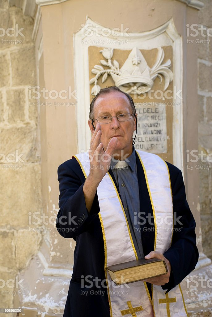 Priest with Bible gives a blessing royalty-free stock photo