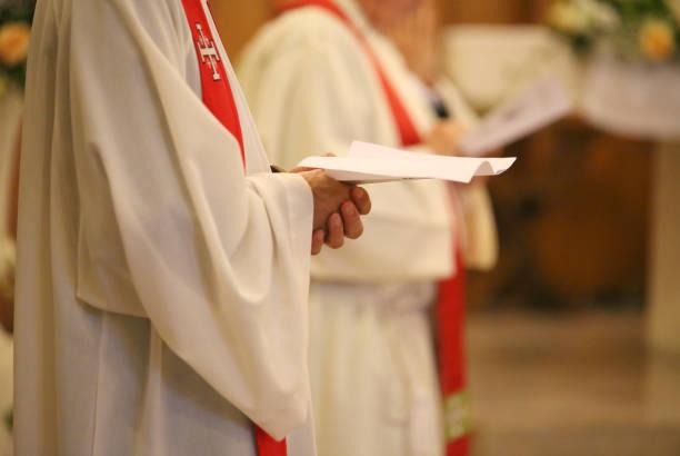 sacerdote com mãos unidas em oração durante a santa missa na igreja - padre - fotografias e filmes do acervo
