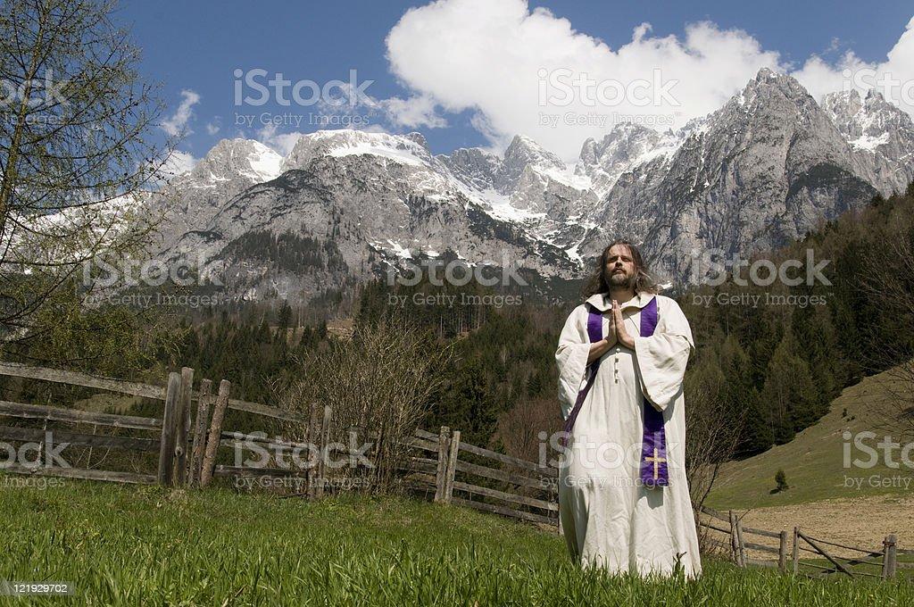 Priester betet auf einer Alm  vor Salzburger Tennengebirge stock photo