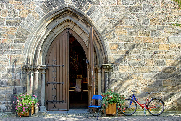 Priest`s bicycle at church entry stock photo