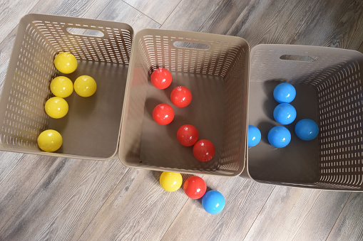 Primary Colored Plastic Balls Sorted into Colors in Bins