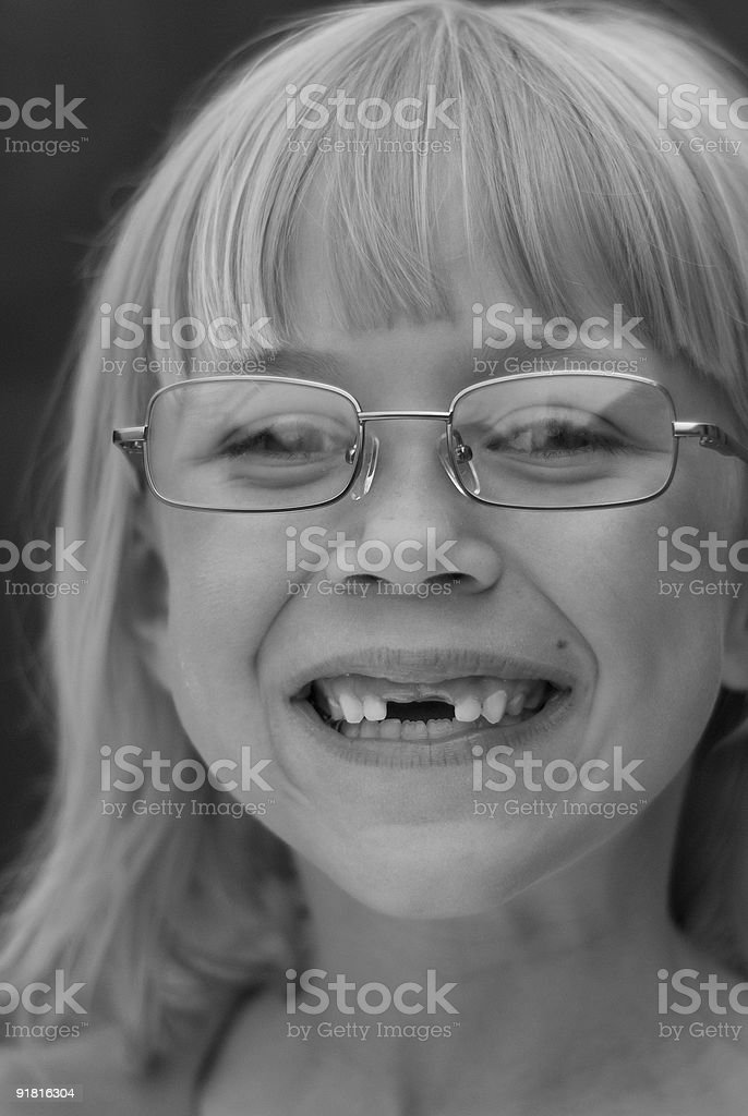 primary school girl missing teeth and wearing glasses stock photo