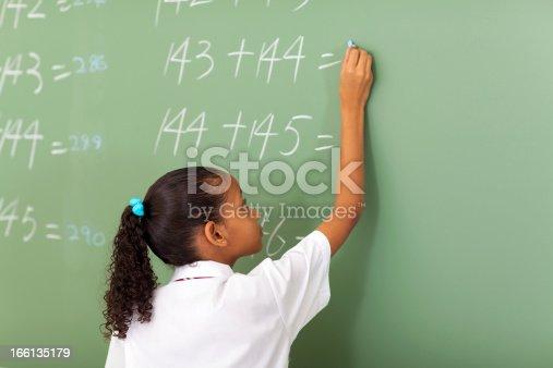 istock primary school girl writing maths answer 166135179