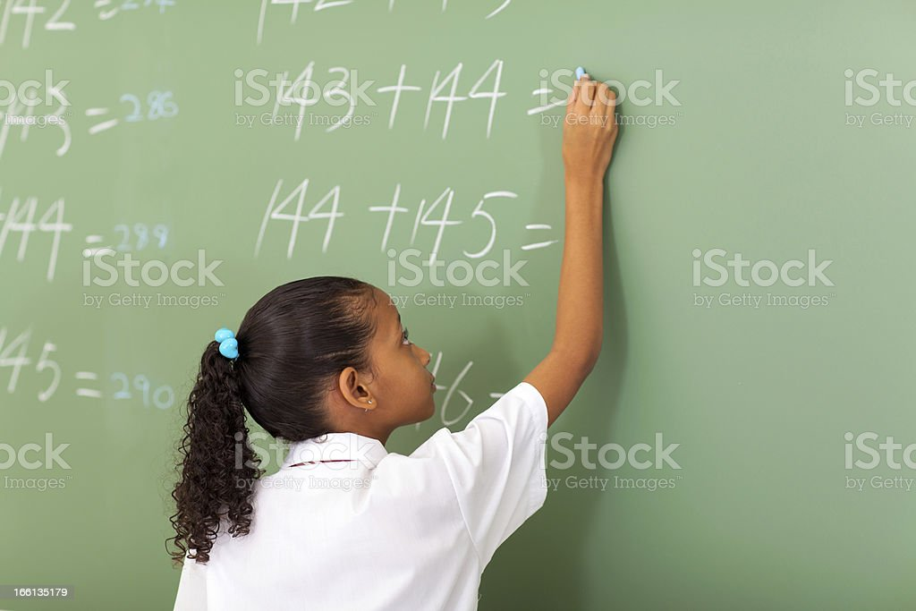 primary school girl writing maths answer stock photo
