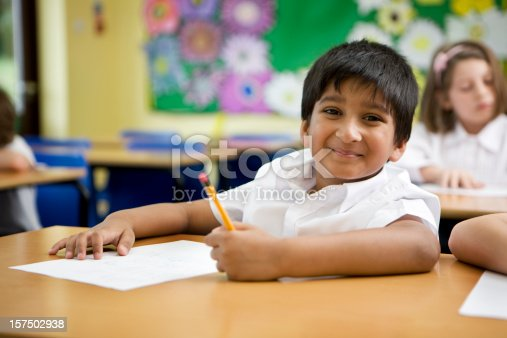 941782244 istock photo primary school: Indian schoolboy happy and carefree in his classroom 157502938