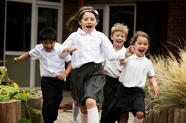 primary school: junior school children running out of their school stock photo