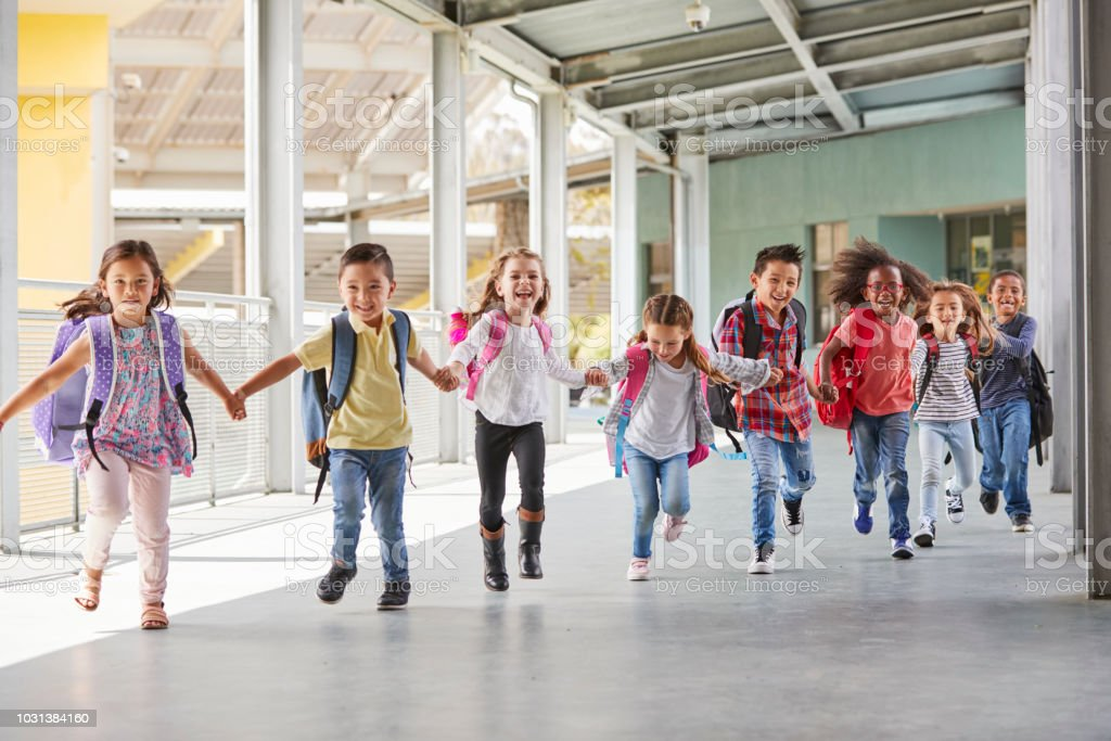 Primary school kids run holding hands in corridor, close up royalty-free stock photo
