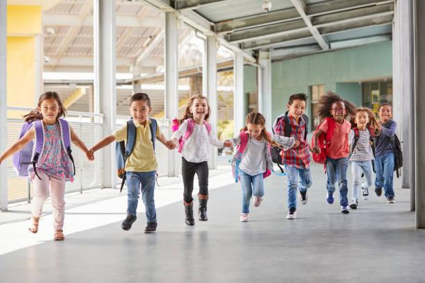 escuela primaria los niños correr cogidos de la mano en el corredor de cerca - escuela primaria fotografías e imágenes de stock