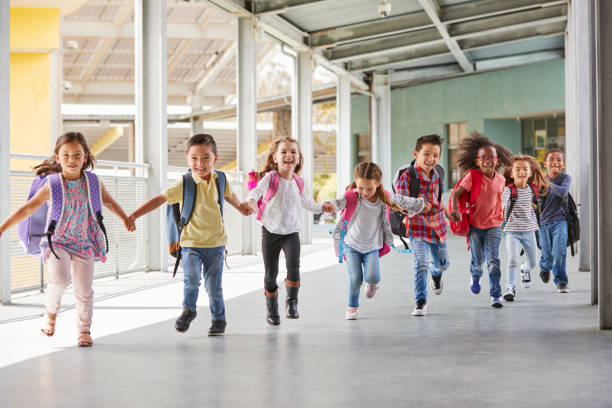 primary school kids run holding hands in corridor, close up - school building stock pictures, royalty-free photos & images
