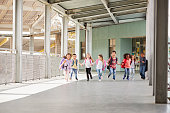 istock Primary school kids run holding hands in school corridor 1031389826