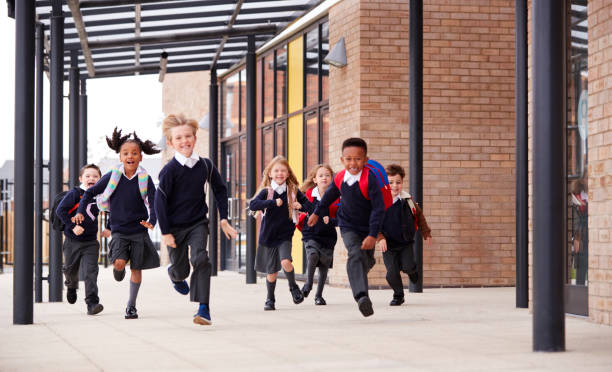 primary school kids, wearing school uniforms and backpacks, running on a walkway outside their school building, front view - primary school stock pictures, royalty-free photos & images