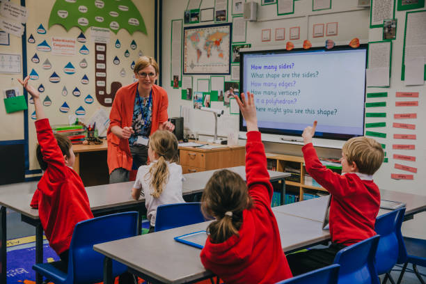 Primary School Lesson Female teacher is teaching shapes to her primary school students. She is asking hem a question and some of the students have their hand in the air to answer. elementary school stock pictures, royalty-free photos & images