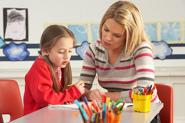 Primary School Pupil And Teacher Working In Classroom stock photo
