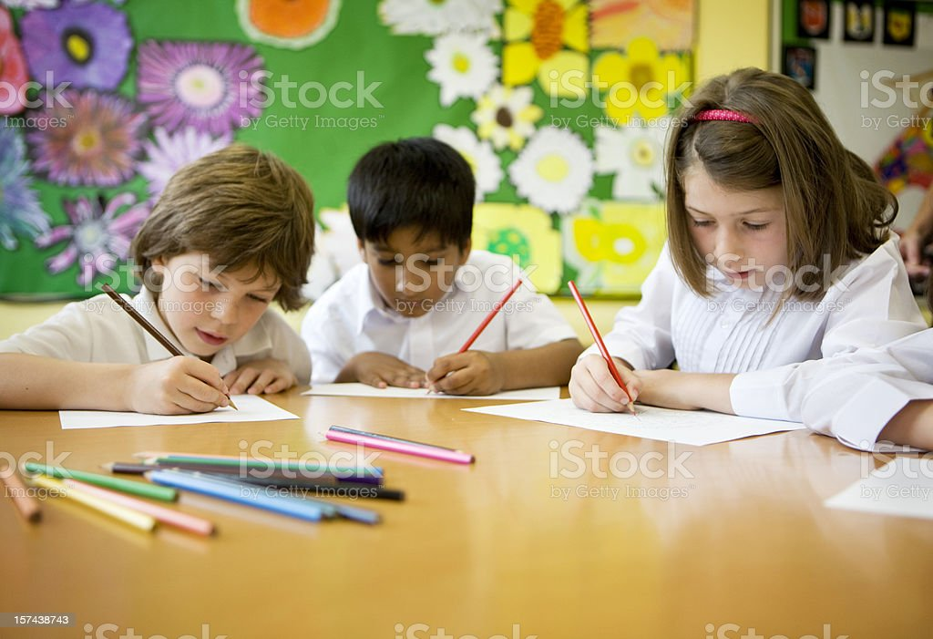 primary school: pupils learning to write in the classroom  6-7 Years Stock Photo