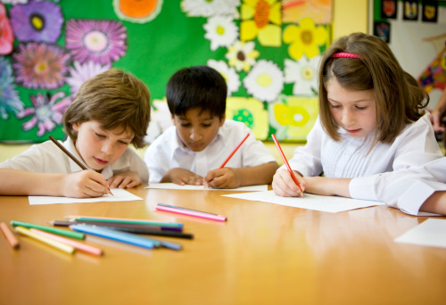 Primary School Pupils Learning To Write In The Classroom Stock Photo - Download Image Now