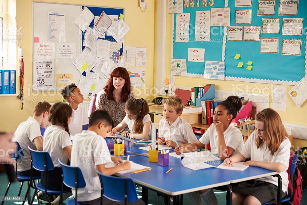 primary school teacher with kids working on a class project royalty free stock photo