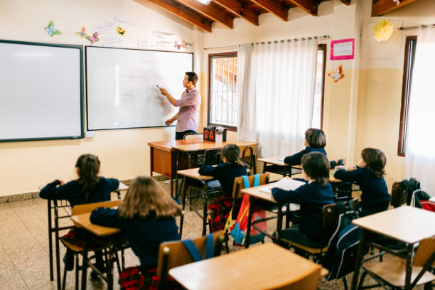 Primary School Teacher working with students in Classroom stock photo