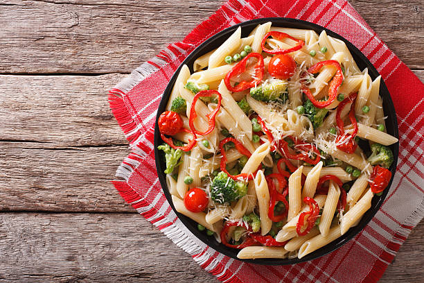 Primavera pasta with vegetables on the table. Horizontal top view Primavera pasta with vegetables on a plate on the table. horizontal top view primavera stock pictures, royalty-free photos & images
