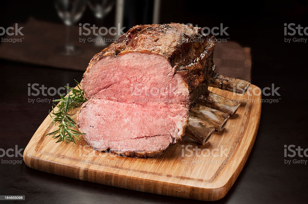 Prime rib roast on a cutting board ready to be sliced stock photo