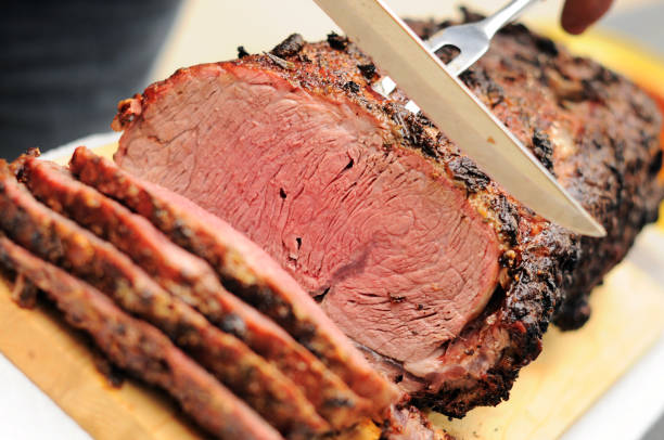 "Prime Rib Roast ""Beautiful prime rib (standing rib) roast being sliced. Crusted with garlic, rosemary and horseradish. Cooked on a barbeque."" horseradish stock pictures, royalty-free photos & images"