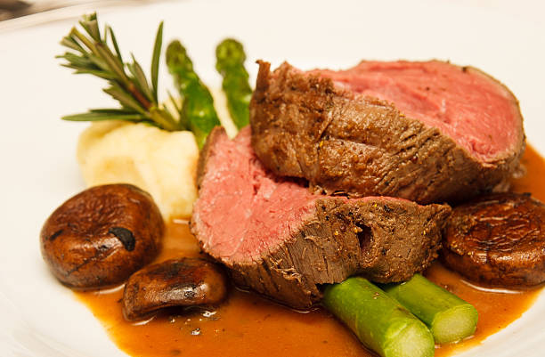 Prime Rib with Asparagus and Mushrooms Rare prime rib beef on a plate with mushrooms, gravy, asparagus, potatoes and rosemary roasted prime rib stock pictures, royalty-free photos & images