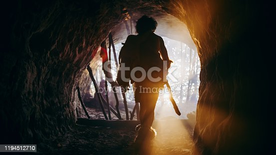 Primeval Caveman in Animal Skin and Fur Holds Stone Tipped Spear Comes out of His Cave into Prehistoric Forest Ready to Hunt. Neanderthal Going Hunting into the Jungle. Shot with Warm Filter.