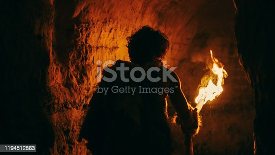 841481956 istock photo Primeval Caveman Wearing Animal Skin Exploring Cave At Night Holding Torch with Fire Looking at Drawings on the Walls at Night. Neanderthal Searching Safe Place to Spend the Night. Back View 1194512863