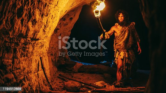 841481956 istock photo Primeval Caveman Wearing Animal Skin Exploring Cave At Night, Holding Torch with Fire Looking at Drawings on the Walls at Night. Neanderthal Searching Safe Place to Spend the Night 1194512869
