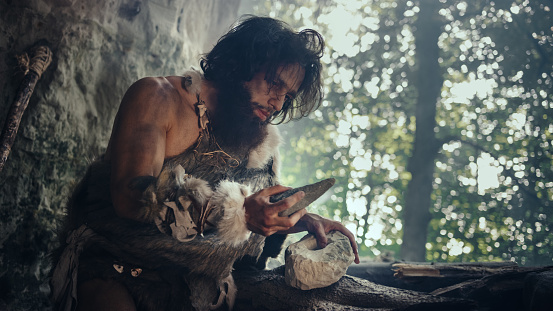istock Primeval Caveman Wearing Animal Skin Holds Sharp Stone and Makes First Primitive Tool for Hunting Animal Prey, or to Handle Hides. Neanderthal Using Handax. Dawn of Human Civilization 1194512725