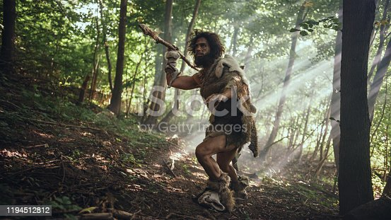 841481956 istock photo Primeval Caveman Wearing Animal Skin Holds Stone Tipped Spear Looks Around, Explores Prehistoric Forest in a Hunt for Animal Prey. Neanderthal Going Hunting in the Jungle 1194512812