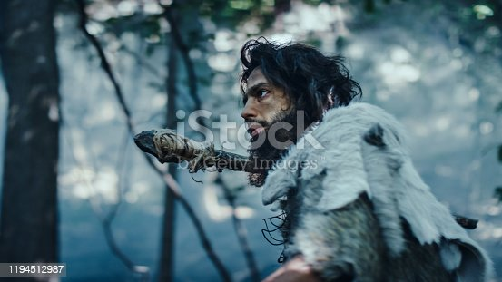 841481956 istock photo Primeval Caveman Wearing Animal Skin Holds Stone Tipped Spear Looks Around, Explores Prehistoric Forest in a Hunt for Animal Prey. Neanderthal Going Hunting in the Jungle in Cold Light 1194512987