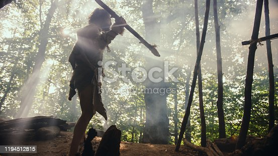 841481956 istock photo Primeval Caveman Wearing Animal Skin Holds Stone Tipped Spear, Stands at the Cave Entrance Looking over Prehistoric Forest Ready to Hunt Animal Preys. Neanderthal Going Hunting in the Jungle 1194512815