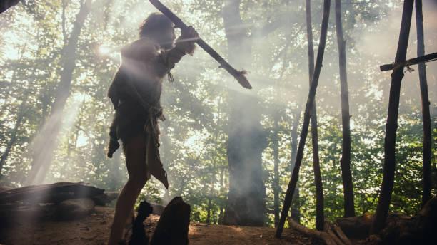 Urzeitliche Höhlenmensch tragen Tierhaut hält Stein gekippt Speer, steht am Höhleneingang Blick über prähistorischen Wald bereit, Tier Beute zu jagen. Neandertaler auf der Jagd im Dschungel – Foto