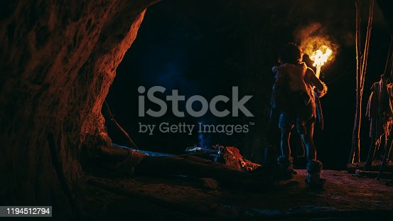 841481956 istock photo Primeval Caveman Wearing Animal Skin Stands in a Cave At Night, Holding Torch with Fire Looking Out of The Cave at Night. Back View 1194512794