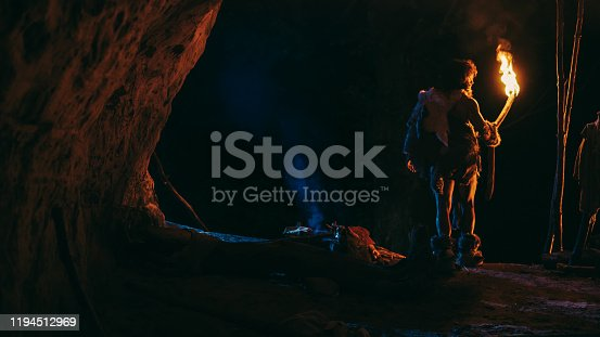 841481956 istock photo Primeval Caveman Wearing Animal Skin Stands in a Cave At Night, Holding Torch with Fire Looking Out of The Cave at Night. Back View 1194512969
