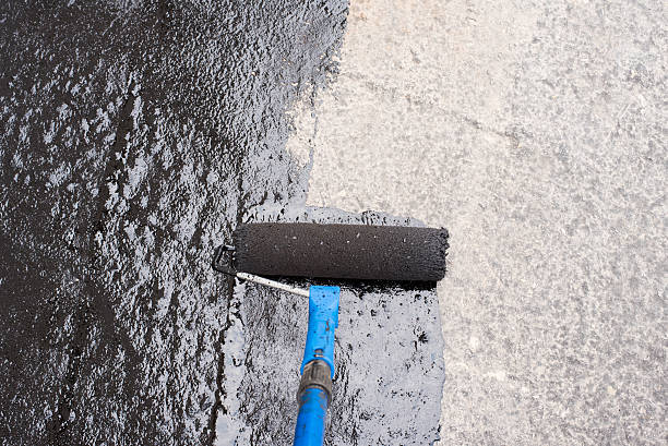 priming  concrete screed .Roller brush. Worker covered surface, bitumen primer for improving adhesion during surfacing,  rolled waterproofing, during the installation of isolation on industrial or household objects waterproof clothing stock pictures, royalty-free photos & images