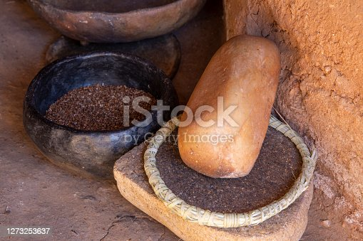 Closeup primitve grinding stone and clay bowl of black sage seed on dirt floor next to adobe wall