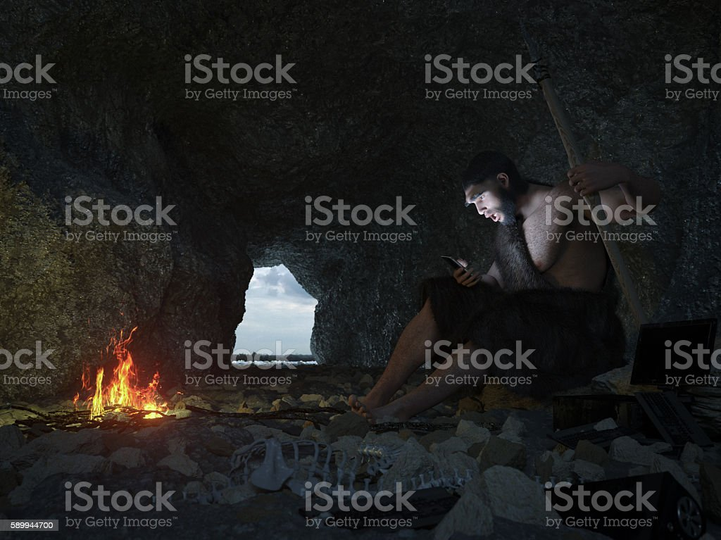 primitive man siting in the cave with smartphone concept illustration stock photo