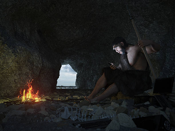 primitive man siting in the cave with smartphone concept illustration - introduction musique photos et images de collection
