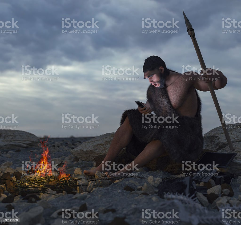 primitive man siting on the stone with smartphone stock photo