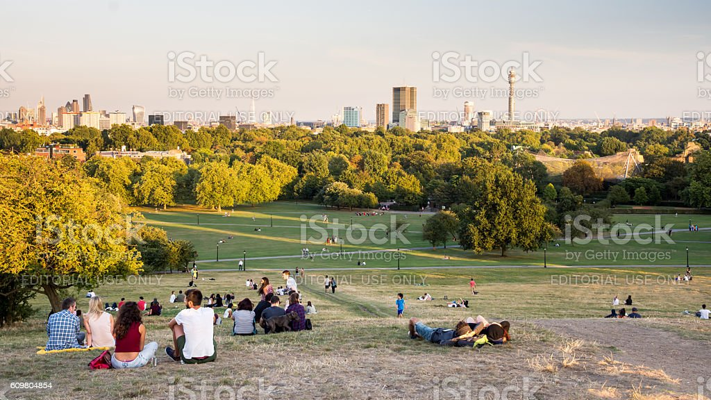 Primrose Hill viewpoint London, England, United Kingdom - August 30, 2016: Crowds gather in the park at Primrose Hill, north London, for the view over London Zoo, Regent's Park, and the London skyline at sunset. Architecture Stock Photo
