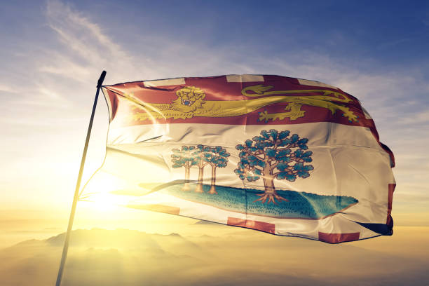 prince edward island province of canada flag textile cloth fabric waving on the top sunrise mist fog - prince edward island stock photos and pictures