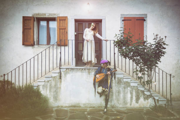 Prince in Renaissance Clothing Serenading To a Young Woman with a Guitar Prince in Renaissance Clothing Serenading To a Young Woman with a Guitar. serenading stock pictures, royalty-free photos & images