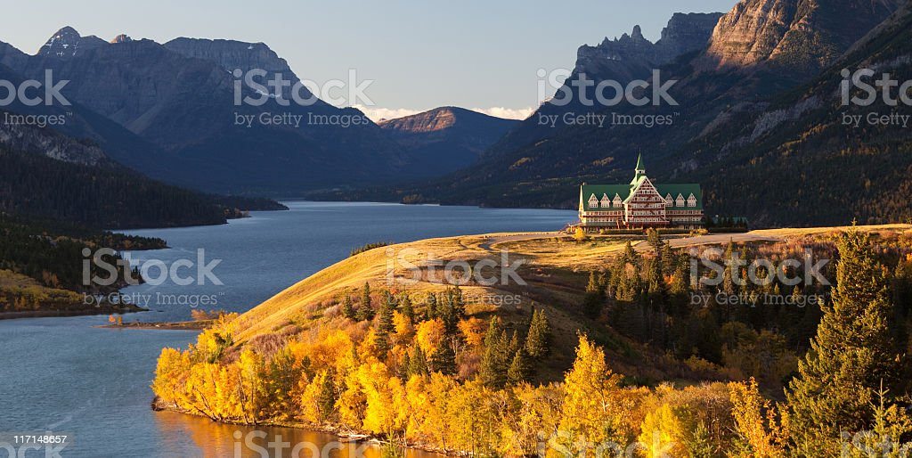 Prince of Wales Hotel in Waterton National Park The iconic Prince of Wales Hotel. Waterton National Park, Alberta, Canada. The famous hotel sits perched on a bluff overlooking waterton lake. This image taken in fall with golden aspens blazing in the warm morning light. This is one of the most scenic locations in all of Alberta and an iconic Rockies scene.  Alberta Stock Photo